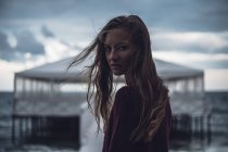 Портрет молодої жінки з flyaway волосся на пристані в сутінках — стокове фото