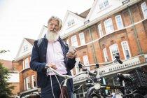 Зріла людина, що стоїть поруч велосипед і тримає смартфон — стокове фото