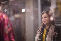 Женщина смотрит и улыбаясь в витрине — стоковое фото
