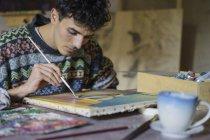 Male artist painting on canvas in artist studio — Stock Photo