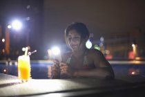 Woman in swimming pool photographing cocktail, Bangkok, Krung Thep, Thailand, Asia — Stock Photo