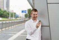 Jovem empresário olhando para o smartphone na cidade, Xangai, China — Fotografia de Stock