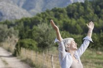 Senior woman, outdoors, arms raised, carefree expression — Stock Photo