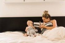 Мама фотографирует маленькую дочь в постели с мягкой игрушкой — стоковое фото