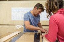 Homme et femme en atelier fabriquant des équipements de ski — Photo de stock