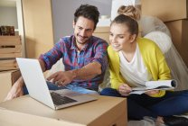 Young couple at new home looking at laptop — Stock Photo