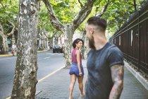 Hipster молодий чоловік і жінка, озираючись назад, на тротуарі, Шанхай Французької концесії, Шанхай, Китай — стокове фото