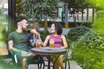 Multi ethnic hipster couple talking at sidewalk cafe, Shanghai French Concession, Shanghai, China — Stock Photo