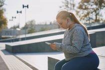 Curvaceous jovem mulher formação e sentado na parede com smartphone — Fotografia de Stock