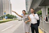 Jeune femme d'affaires et homme d'affaires saluant taxi dans la ville, Shanghai, Chine — Photo de stock