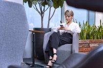 Бізнес-леді сидячи на стілець в офісі і за допомогою смартфона — стокове фото