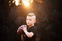 Portrait of boy holding american football ball in garden — Stock Photo