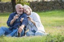 Casal sênior ao ar livre, sentado em cobertor, desfrutando de copo de vinho — Fotografia de Stock