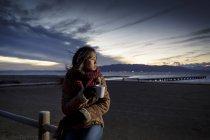 Mujer joven envuelta en bufanda mirando desde la playa al atardecer - foto de stock