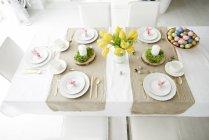 Tovaglioli di orecchio di coniglio e ciotola di uova di Pasqua colorate sul tavolo da pranzo — Foto stock
