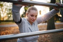 Portrait of curvaceous woman training against handrail in park — Stock Photo