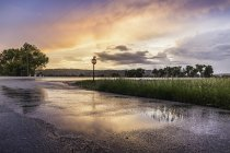 Puesta de sol reflejada en carretera mojada, Montana, EE.UU. - foto de stock