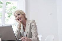 Femme d'affaires, la main sur le menton à la recherche de suite souriant — Photo de stock