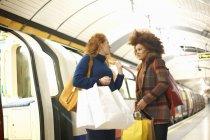 Duas jovens mulheres na plataforma de trem subterrâneo segurando sacos de compras — Fotografia de Stock
