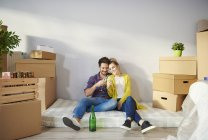 Young couple surrounded by cardboard boxes drinking champagne — Stock Photo