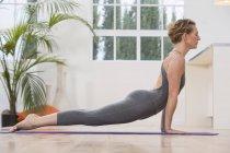 Visão lateral da mulher em casa fazendo ioga — Fotografia de Stock