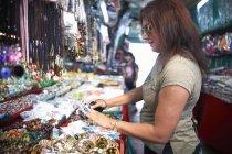 Frau betrachtet Souvenirs am Marktstand, Bangkok, Krung Thep, Thailand, Asien — Stockfoto