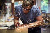 Человек в мастерской по изготовлению лыжного оборудования — стоковое фото