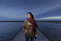 Young woman walking on pier at dusk — Stock Photo
