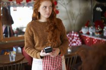 Serveuse dans un café tenant un lecteur de carte de crédit — Photo de stock