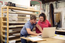 Man and woman using laptop in workshop — Stock Photo