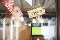 Woman small business owner turning open sign — Stock Photo