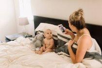 Mère prenant une photo de bébé fille assise dans son lit avec un jouet doux — Photo de stock