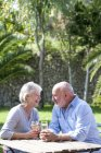 Senior couple sitting in garden, enjoying glass of wine — Stock Photo