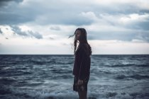 Портрет молодой женщины, стоящей на пляже в сумерках — стоковое фото