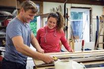 Mann und Frau in Werkstatt für Skiausrüstung — Stockfoto