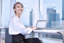 Молодая предпринимательница с ноутбуком улыбается в камеру — стоковое фото