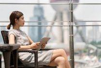 Joven empresaria con tableta digital en el café de la acera en Shanghai, China - foto de stock