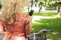 Жінка з велосипеда за допомогою смартфона — стокове фото