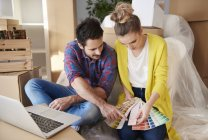 Young couple at home looking at paint swatches — Stock Photo