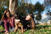 Две молодые женщины обнимают собаку — стоковое фото