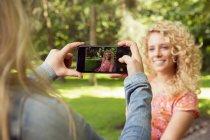 Femme prenant la photo d'un ami en utilisant un smartphone — Photo de stock
