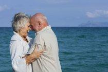 Старшая пара обнимается и смеется на берегу моря — стоковое фото