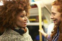 Duas jovens no metrô sorrindo uma para a outra — Fotografia de Stock