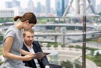 Пара молодих бізнес дивлячись на цифровий планшет на тротуарі кафе, Шанхай, Китай — стокове фото