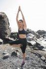 Молода жінка заняттях йогою на пляжі — стокове фото