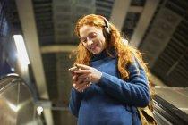 Giovane donna sulla scala mobile guardando smartphone — Foto stock