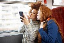 Zwei junge Frauen machen Selfie im Zug — Stockfoto