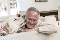 Golden retriever licking smiling mans face — Stock Photo