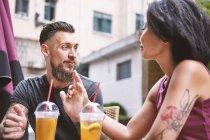 Розрахована на багато етнічні hipster пара говорити на тротуарі кафе, Французька концесія Шанхай, Шанхай, Китай — стокове фото