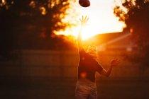 Хлопчик практикуючих американського футболу в саду і досягнення Спіймати м'яч — стокове фото